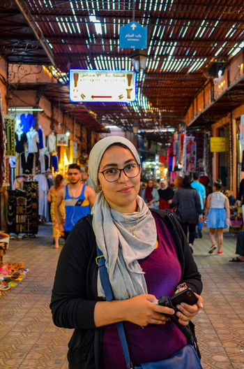 Portrait of smiling woman with smart phone in city