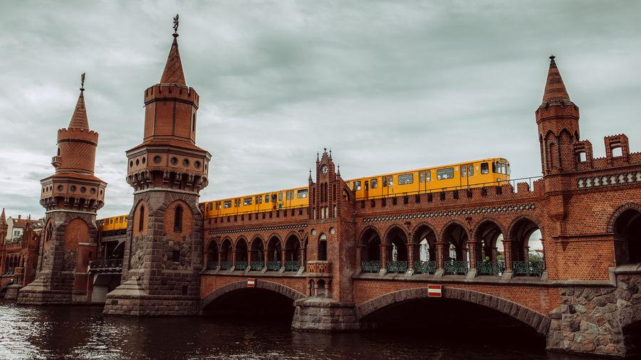 Train On Oberbaum Bridge Over Spree River Against Sky In City