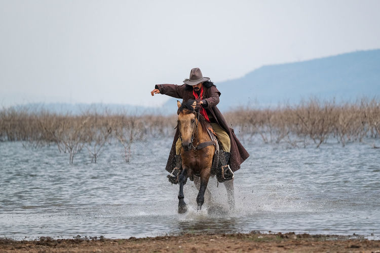 A man in a cowboy outfit with his horse Animal Water Domestic Domestic Animals Mammal Animal Themes Pets Vertebrate One Animal Sky Nature Day Animal Wildlife Land Motion Running Scenics - Nature Livestock Sea Outdoors Riding