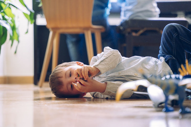 Portrait of happy boy lying down on floor