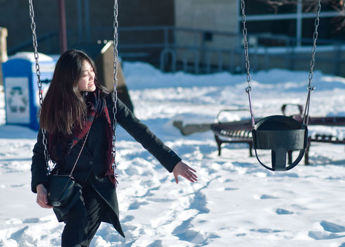 Woman sitting on swing during winter