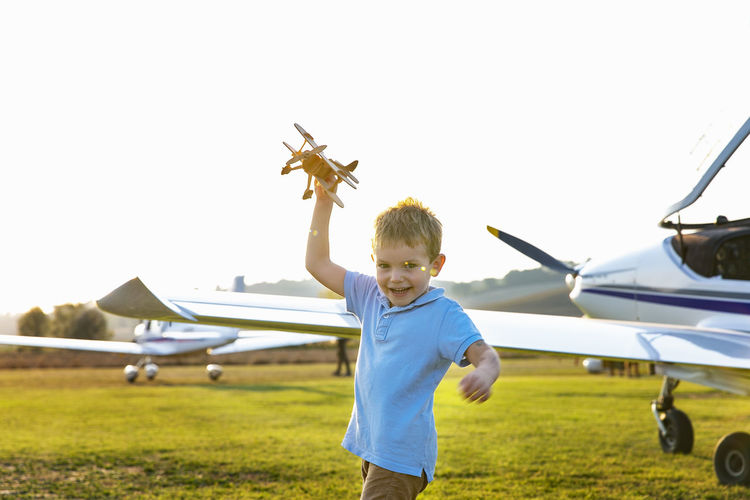 Full length of boy sitting on airplane on field against sky