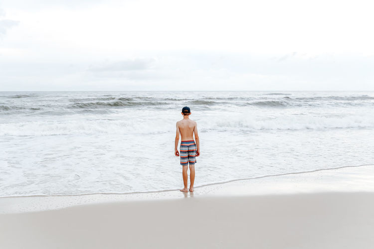 Full length rear view of shirtless man on beach