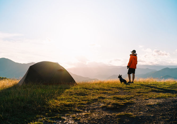 Full length of man and french bulldog by a tent on field against mountains and sky at sunset