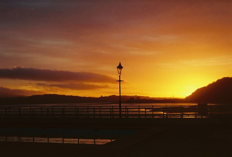 Sunset in Beaumaris (december 2016) Beauty In Nature Day Mountain Nature No People Outdoors Road Scenics Sea Silhouette Sky Street Light Sunset Water Neon Life Paint The Town Yellow