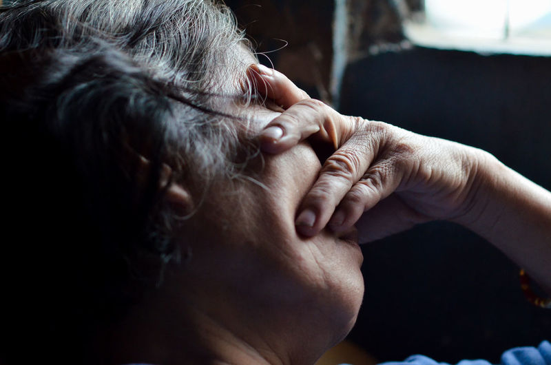 Close-Up Of Depressed Woman Covering Eyes At Home