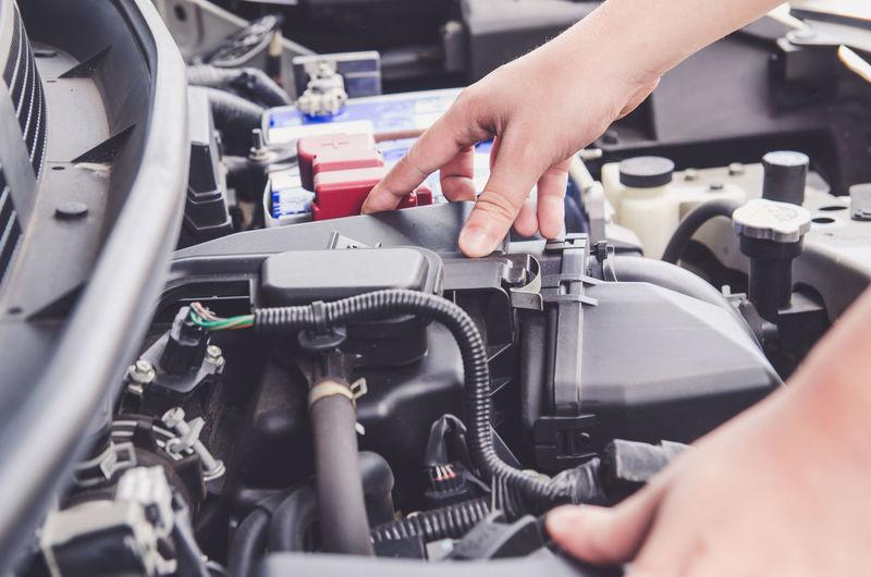 Cropped Hands Of Mechanic Repairing Car At Auto Repair Shop