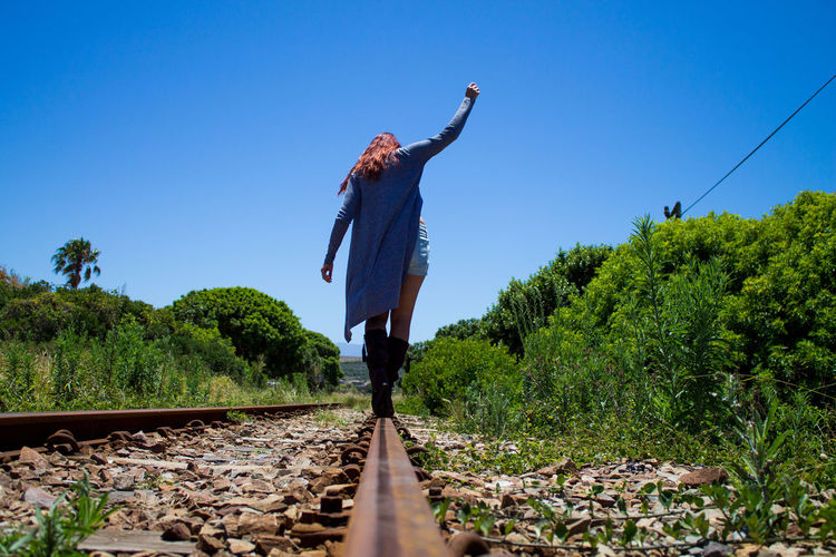 Person standing by railroad track against clear blue sky