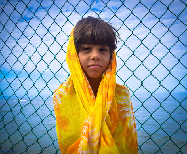 Portrait of boy covered with fabric against chainlink fence by sea