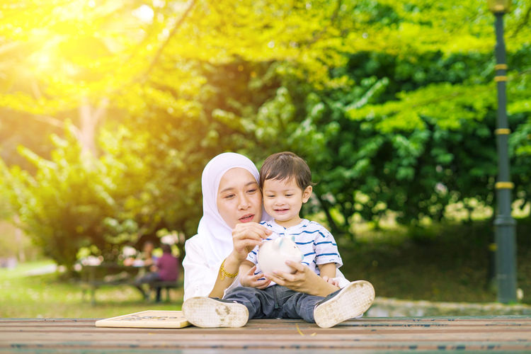 Young woman with her cute son learn how to put coins into piggy bank. Future planning concept. Child Childhood Togetherness Family Males  Men Bonding Son Innocence Two People Boys Emotion Portrait Offspring Sitting Tree Happiness Smiling Positive Emotion Day Casual Clothing Sister