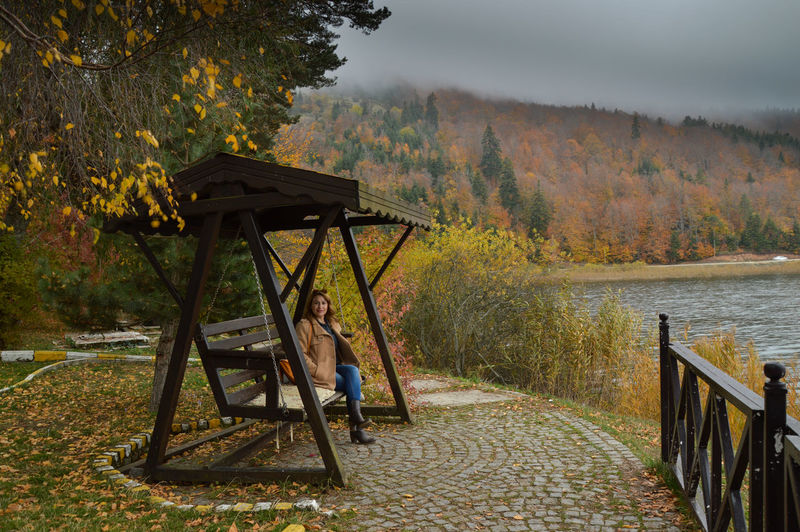 Portrait of woman sitting on wooden swing by river