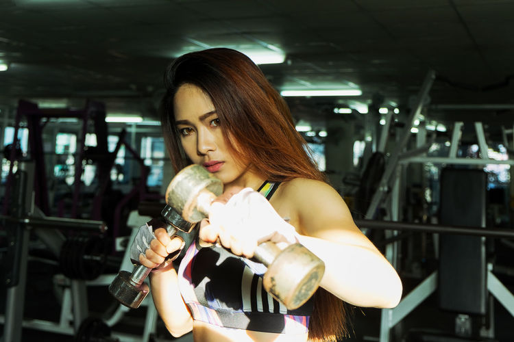 Confident Young Woman Exercising At Gym