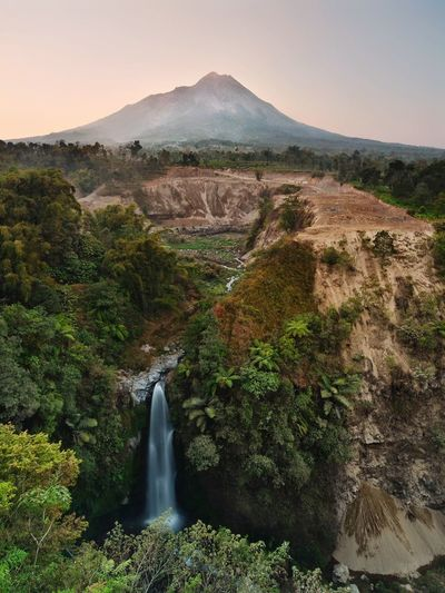 Scenic view of waterfall against sky at merapi mountain indonesian