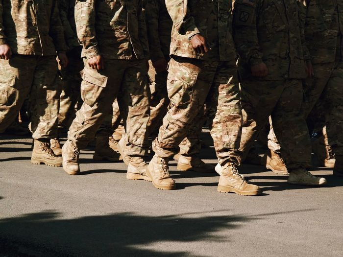 Low section of army soldiers walking on street
