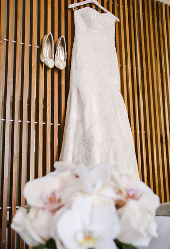Wedding dress hanging on wood next to shoes with bouquet flowers out of focus in the foreground
