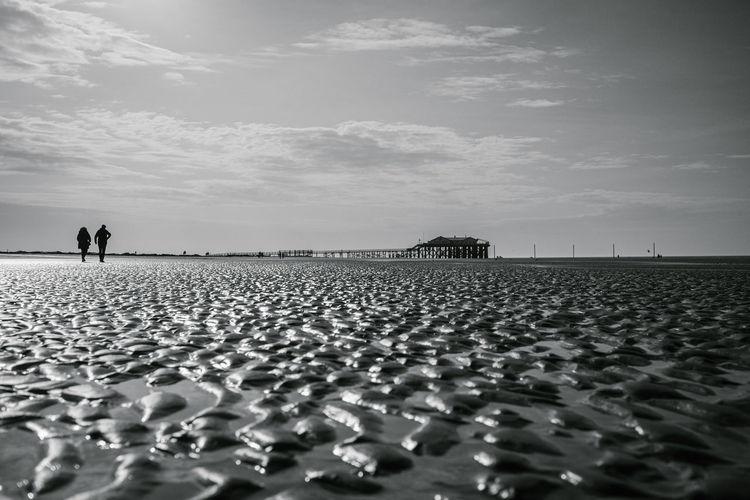 People standing on pebbles on field against sky