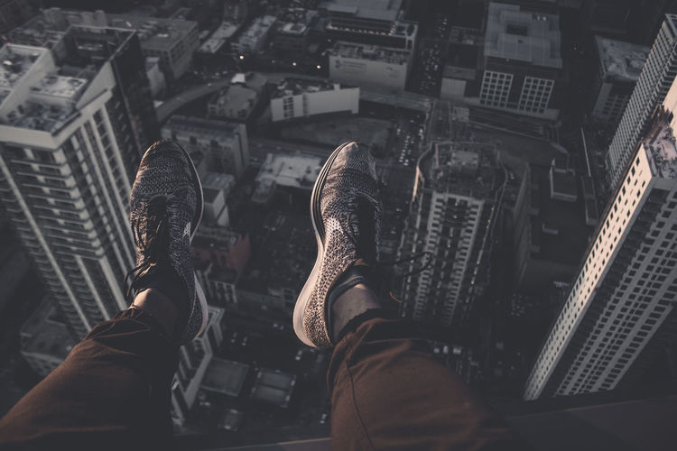 Low section of man sitting on building terrace over cityscape