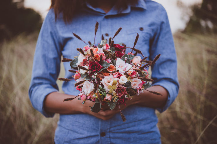 Midsection Of Woman Holding Bouquet On Field