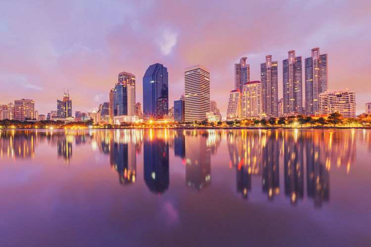 Reflection of illuminated buildings in river against sky during dusk