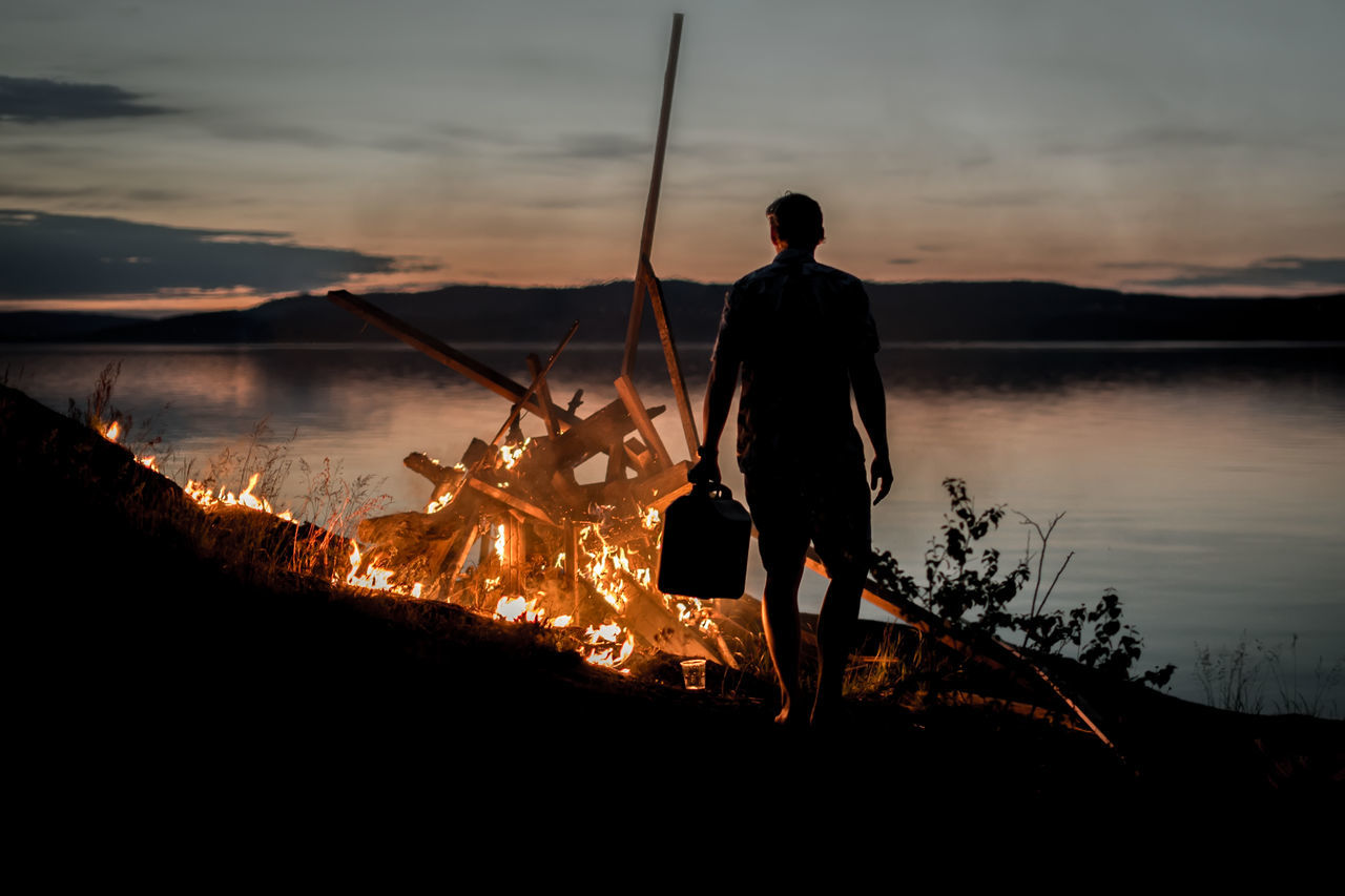 Rear view of man standing in front of campfire by lake