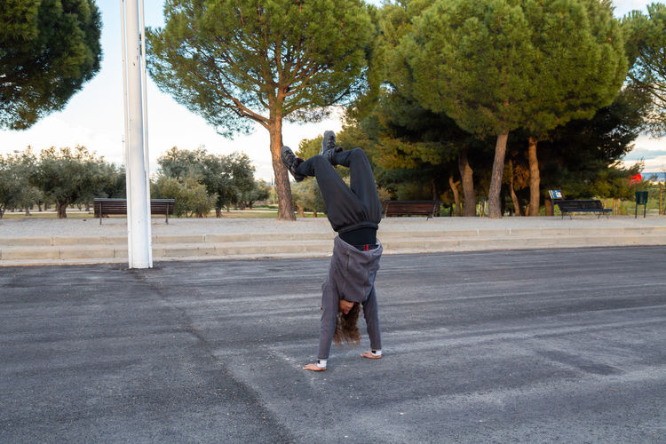 Rear view of man photographing on road