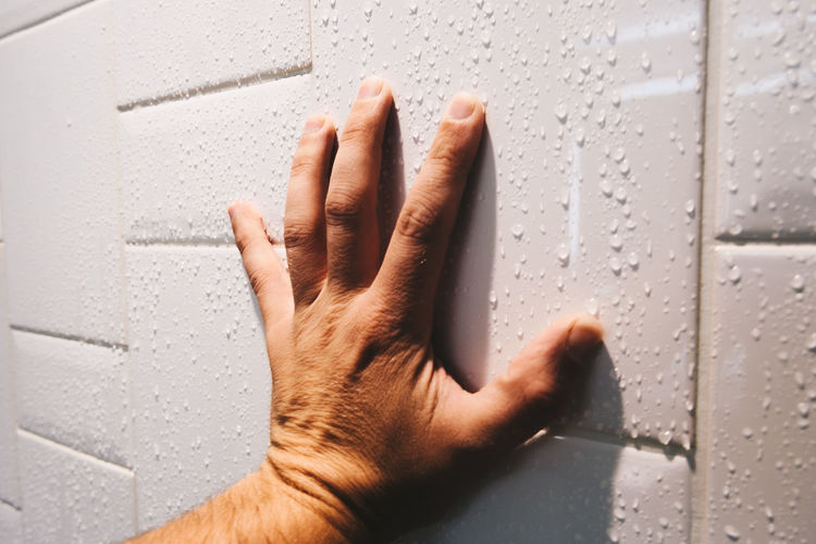Close-up of hand on wet wall
