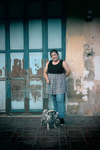 Full length portrait of woman standing against building