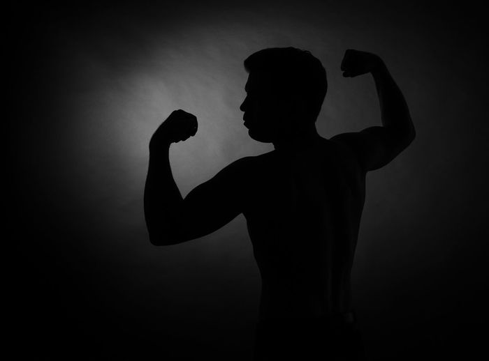 Silhouette of man flexing muscles against black background