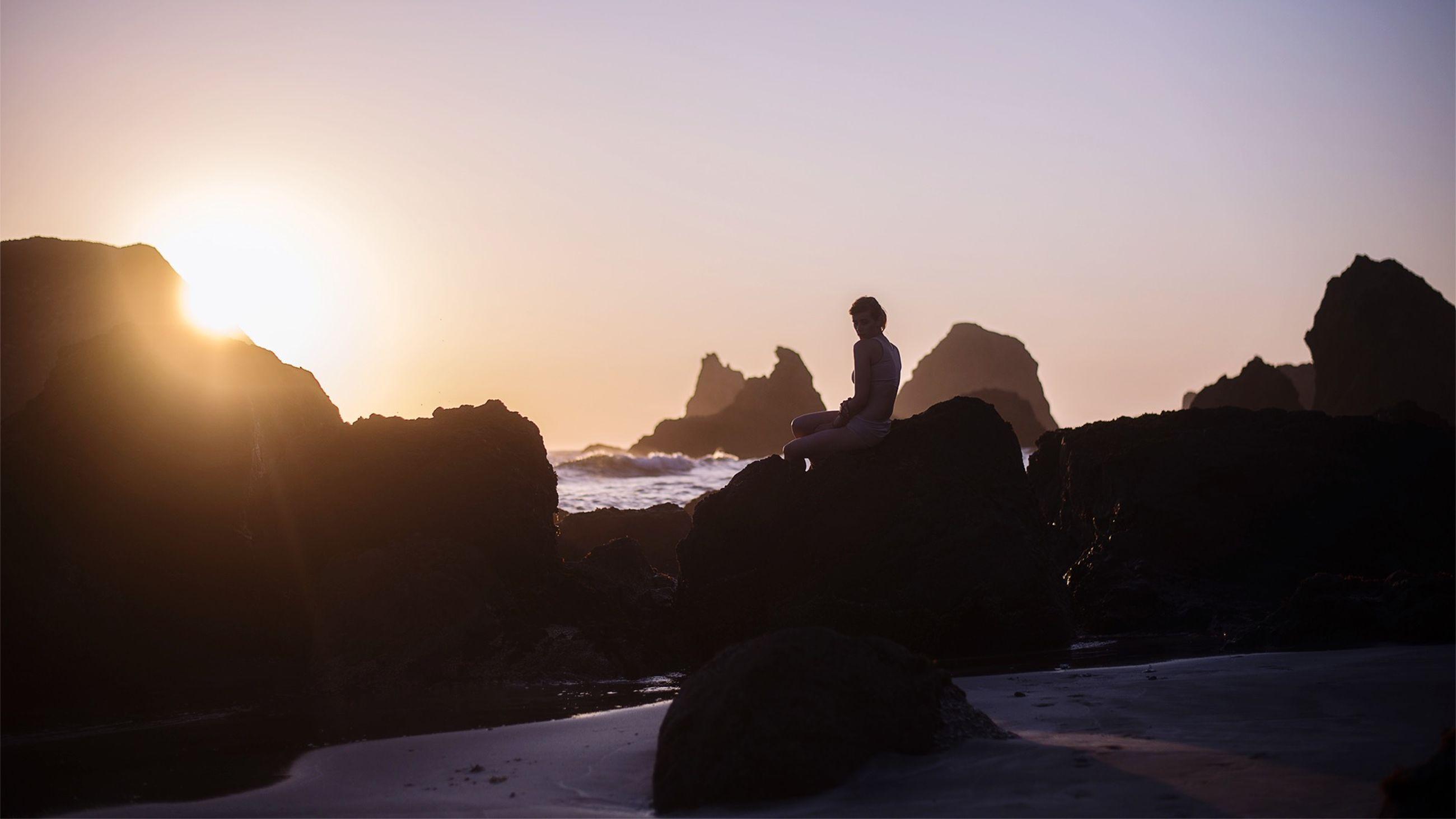 sun, sunset, lifestyles, clear sky, leisure activity, sunlight, men, silhouette, sunbeam, rock - object, sea, lens flare, copy space, beach, scenics, water, vacations, sky