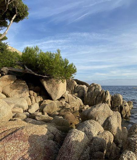 Rocks by sea against sky