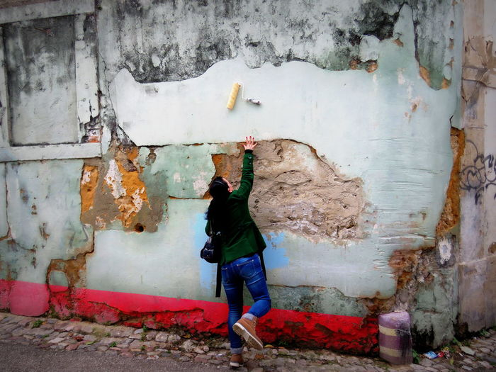 Rear View Of Woman Hand Reaching Towards Paint Roller On Damaged Wall