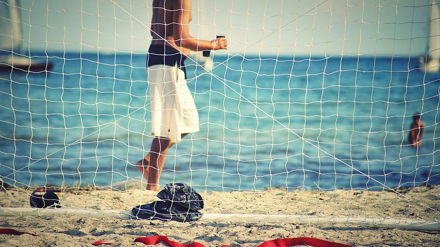 Low section of shirtless man standing at beach seen through net