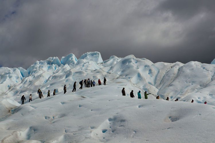 Low angle view of people walking at perito moreno glacier against cloudy sky
