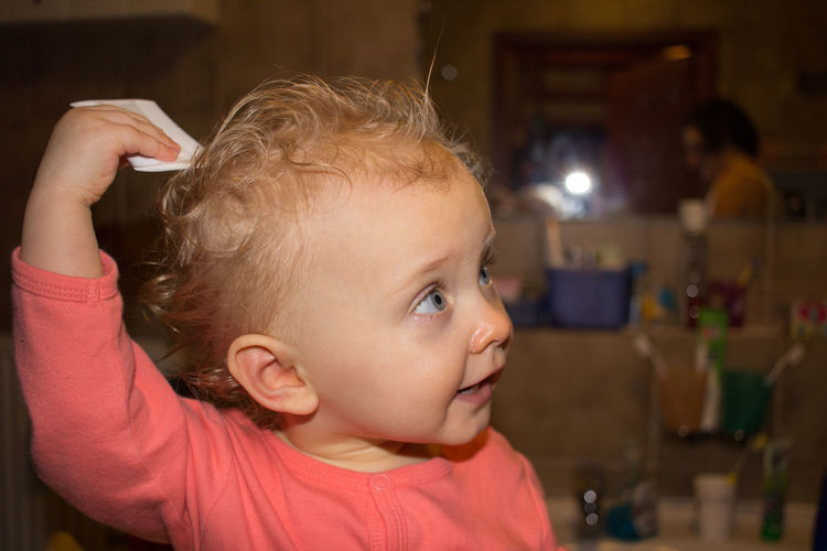 Cute baby girl combing hair at home
