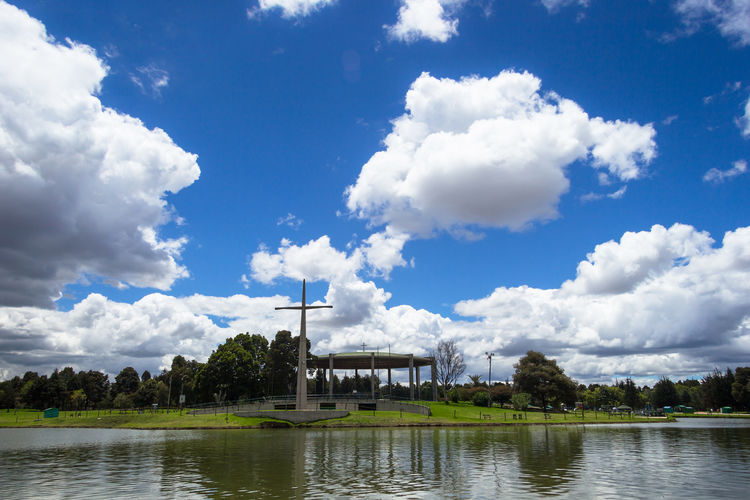"""Landscape view of lake at """"Simon Bolivar"""" central park. Architecture Beauty In Nature Building Exterior Built Structure Catholic Central Park Cloud - Sky Cross Day Forest Green Color Lake Landscape Nature Nature No People Outdoors Park Simon Bolivar Park Sky Tree Water Water Reflections"""