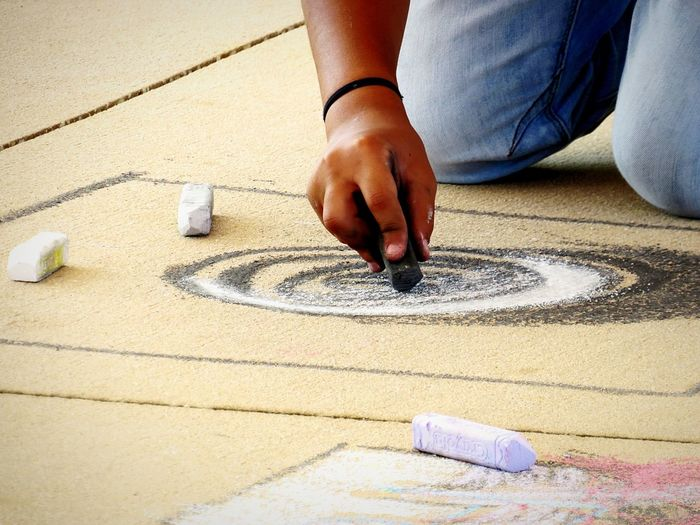 Midsection of person drawing with chalk on cardboard