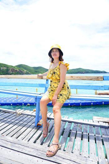 Portrait of woman sitting on sea against sky