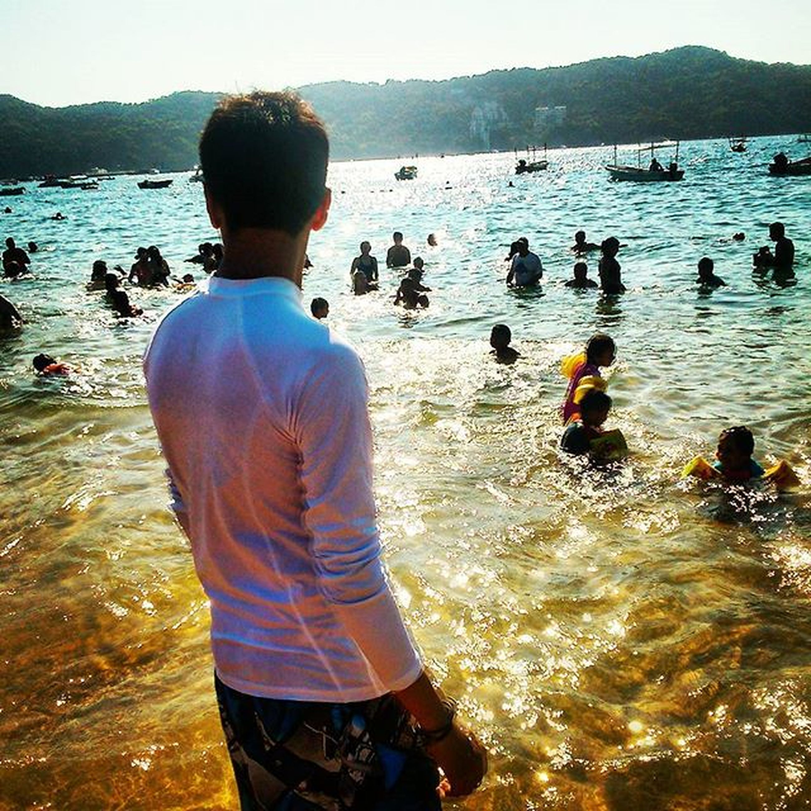 water, lifestyles, leisure activity, sea, beach, rear view, togetherness, men, mountain, shore, scenics, vacations, beauty in nature, standing, person, tranquility, nature, lake, tranquil scene