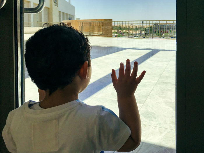 Baby Babyboy Childhood Door Goodbye Hand Hi5 Human Hand Look Look Out Look Out The Window Look Outside Looking Looking Out Looking Out Of The Window One Person Outdoors People Real People Small Window