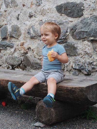 Cute boy sitting on rock