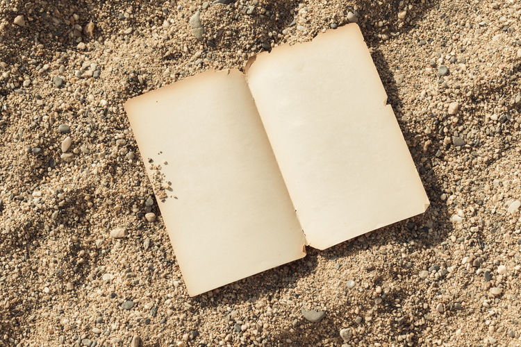 High angle view of book on sand