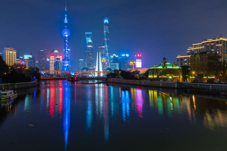 Illuminated Skyscrapers By Huangpu River In City At Night