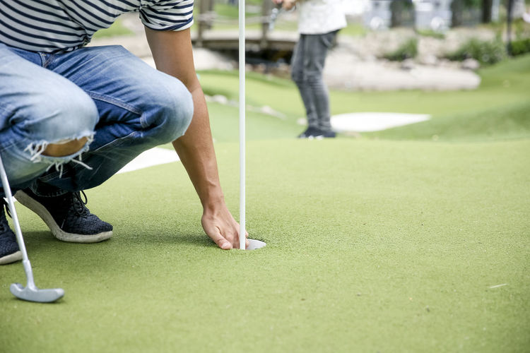 Low section of man playing on golf course