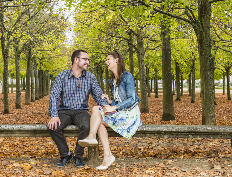 Lovely couple having fun together on a stone bench in a park in autumn. Bench In The Woods Couple Dating Fun Happiness Happy Love Lovers Autumn Casual Clothing Cheerful Friendship Loughing Outdoors Park - Man Made Space Real People Sitting Smiling Togetherness Two People Young Adult Young Women