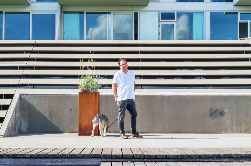 Man with dog standing in front of building