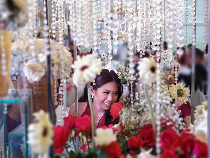 Close-up of flowers against woman smiling in store
