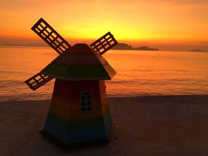 Lifeguard hut on beach during sunset