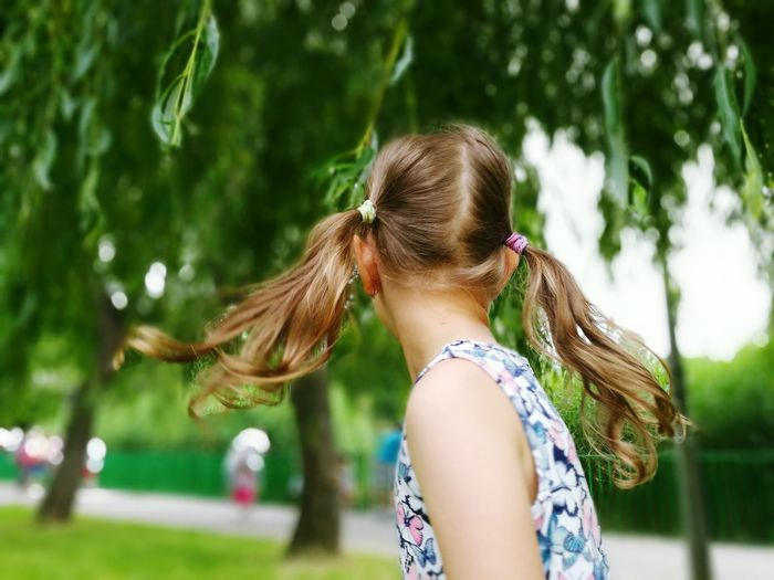 Side view of girl with pigtails against trees at park