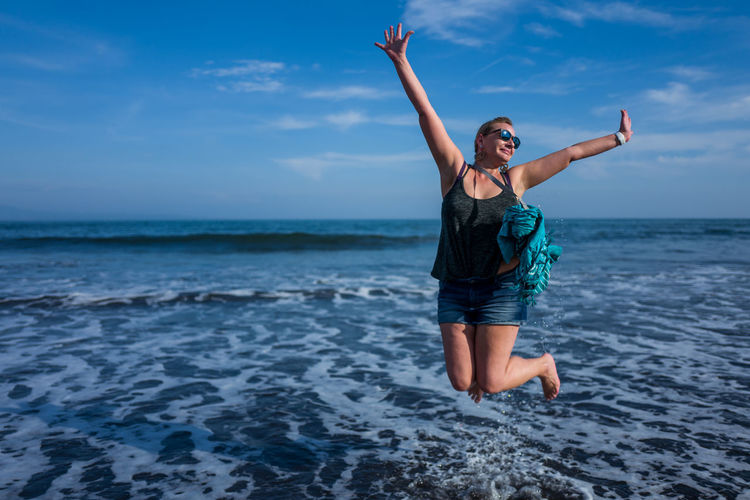 Full Length Of Mature Woman Jumping On Shore At Beach Against Sky