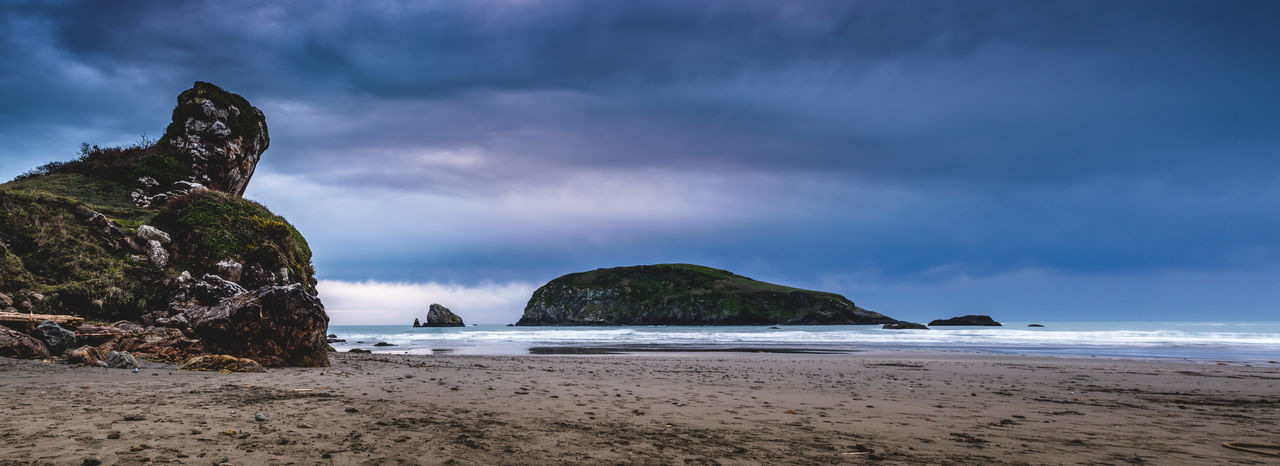 Panoramic view of beach against stormy clouds